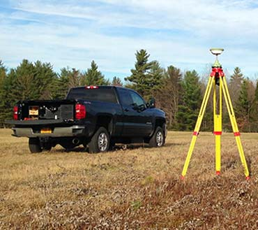 Truck and land survey equipment in upstate NY field
